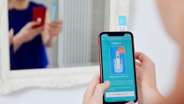 woman using TestCard app in bathroom